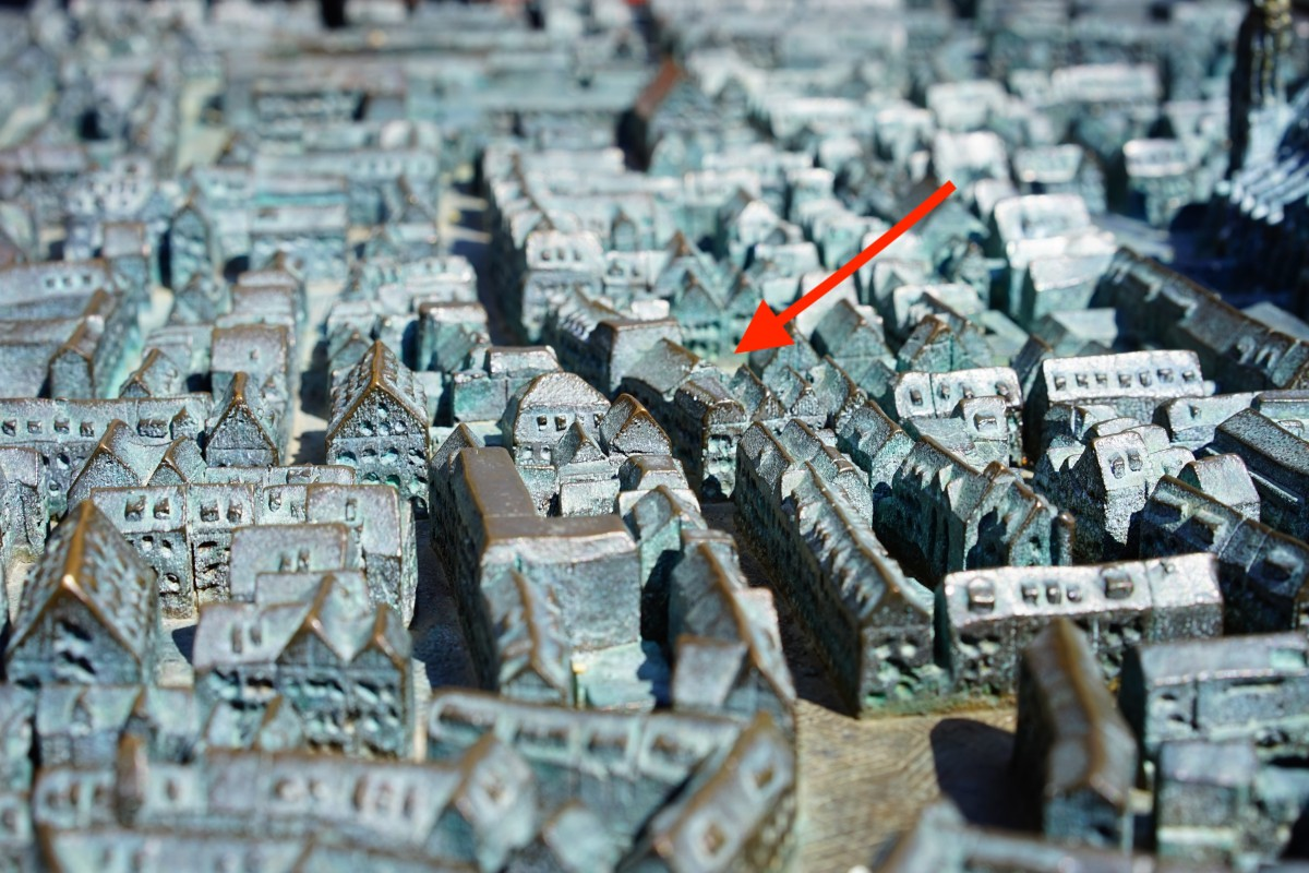 Ein roter Pfeil zeigt auf einen Ort in einer Stadt aus Metall
