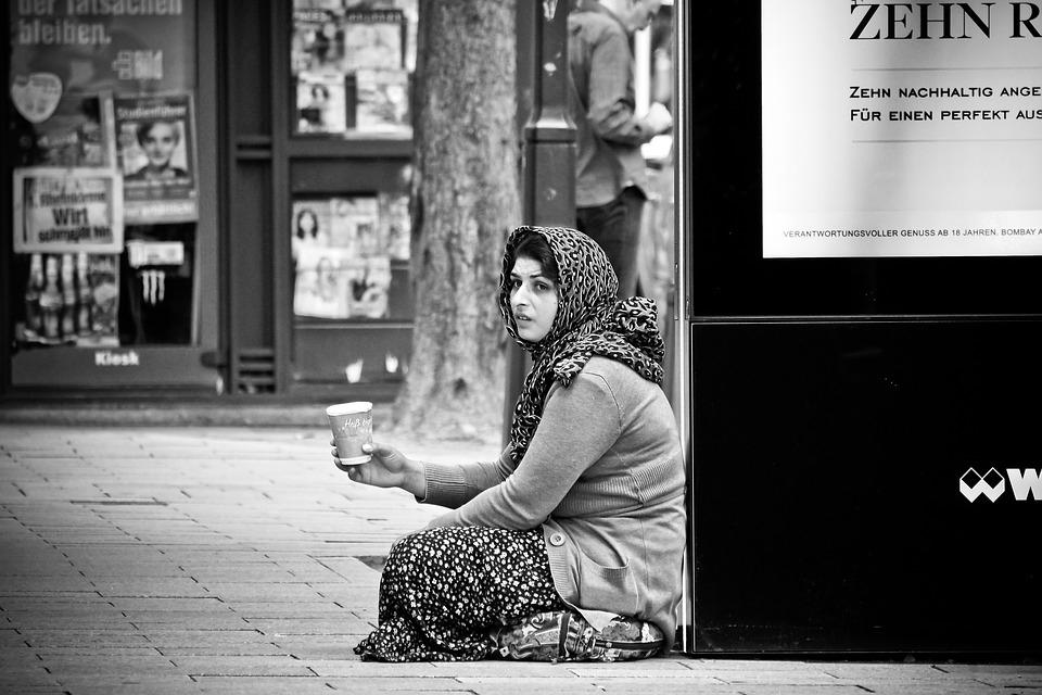 Auf dem Bild ist eine Bettlerin. Sie sitzt auf ihren Knien. Sie hat einen Becher für Kleingeld.