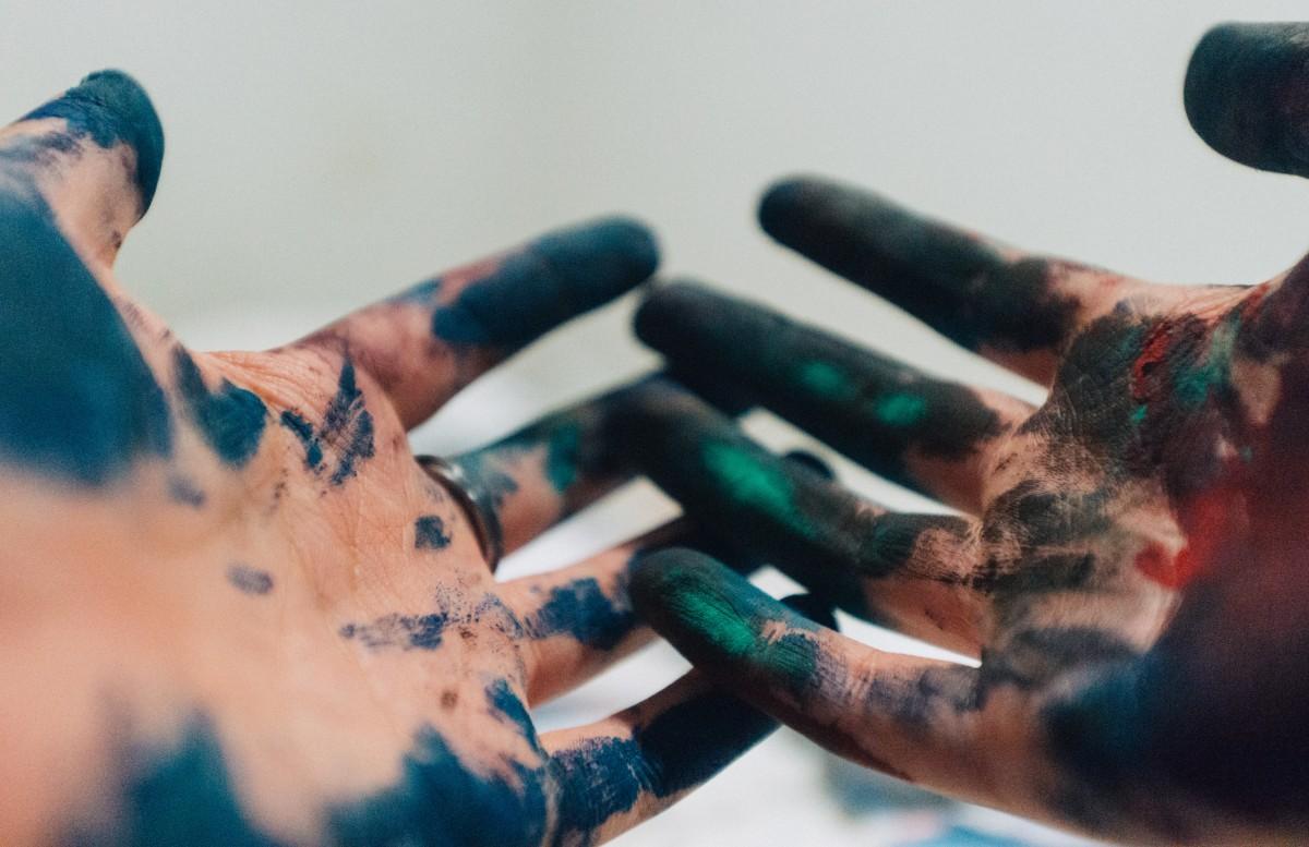 Auf dem Bild sind zwei Hände zu sehen. Die Hände sind mit Farbe bemalt.