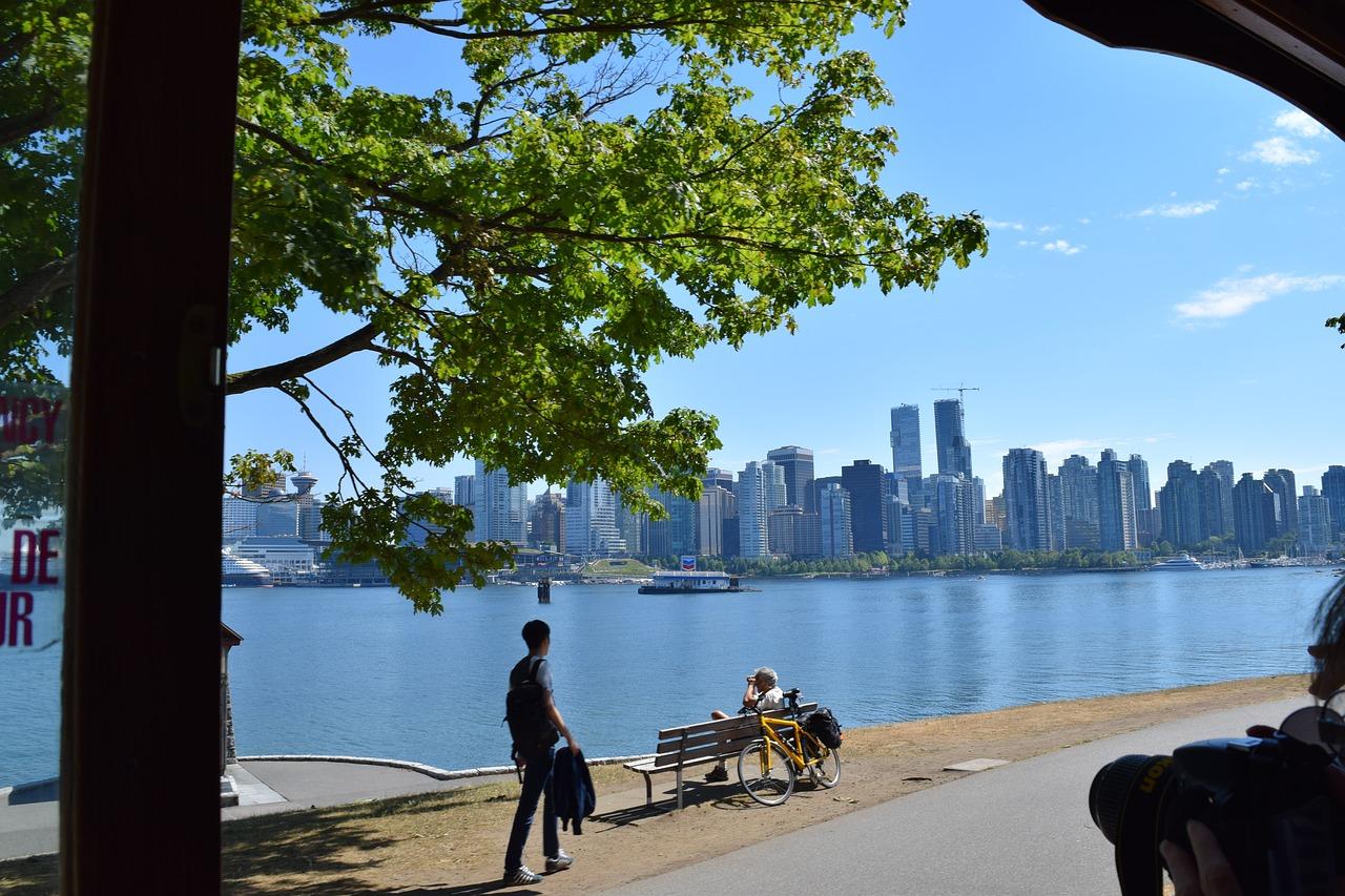 Auf dem Bild ist ein Park in der Stadt Vancouver zu sehen. Man sieht Hoch·häuser, das Meer und 2 Personen.
