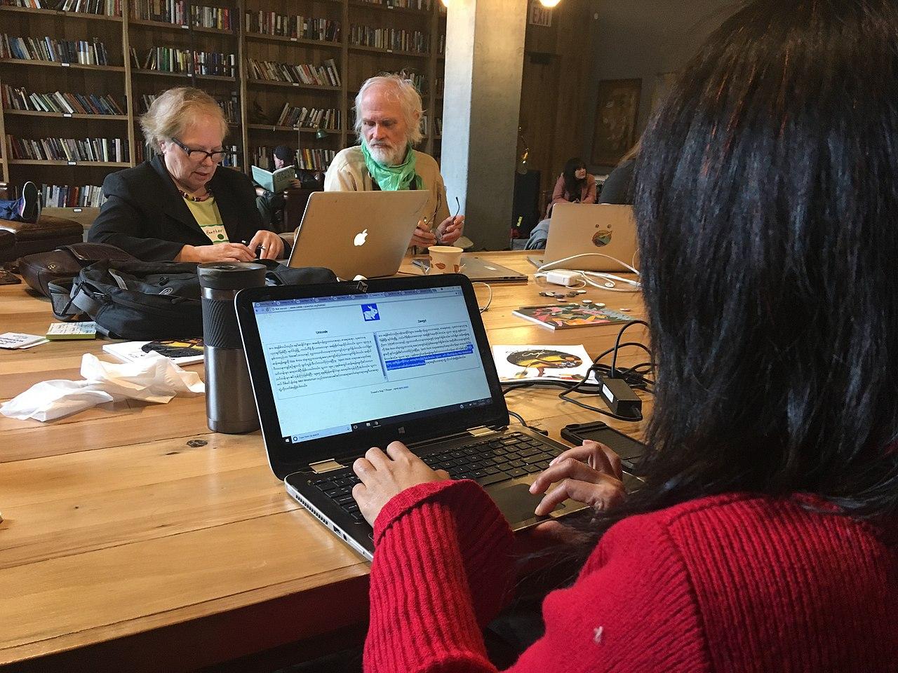Auf dem Bild sind Personen beim Übersetzen von Texten zu sehen, am Computer