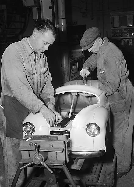 Auf dem Bild sind 2 Männer zu sehen. Sie arbeiten an einem Mini·auto.