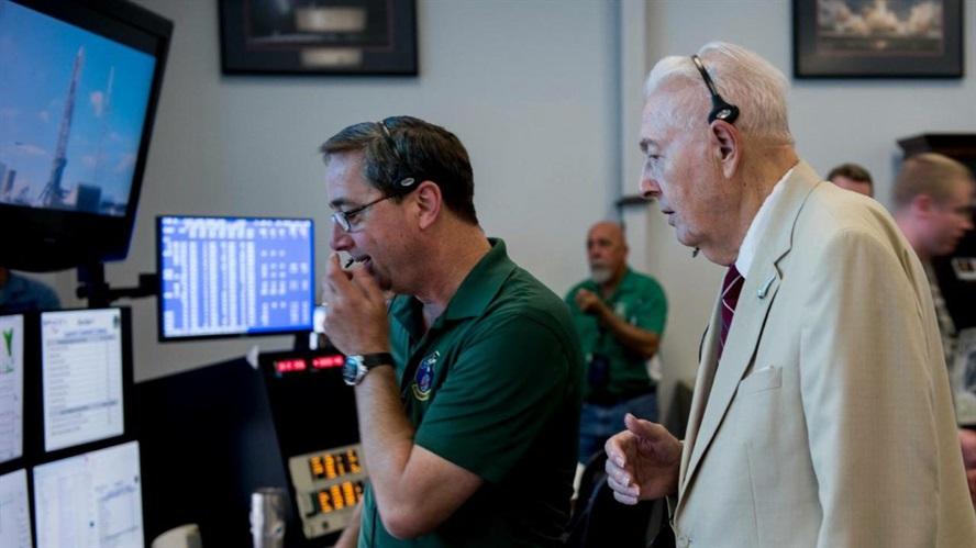 auf dem Bild sind 2 Männer beim Start von einem Satellit zu sehen