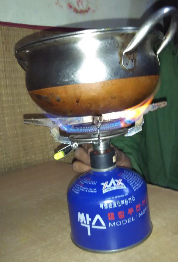 Auf dem Bild ist ein Gas·kocher und ein Topf zu sehen