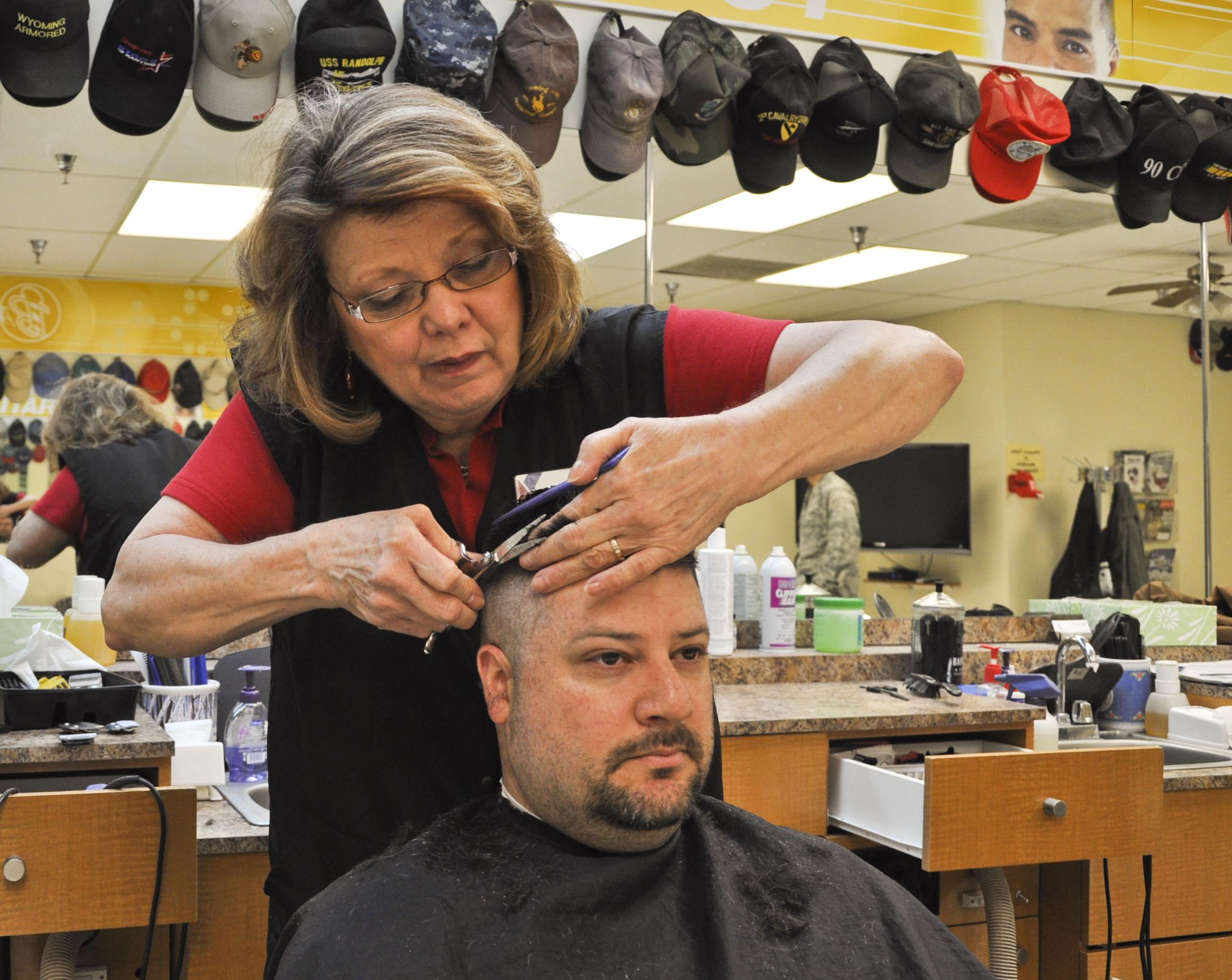 auf dem Bild schneidet eine Frau einem Mann die Haare