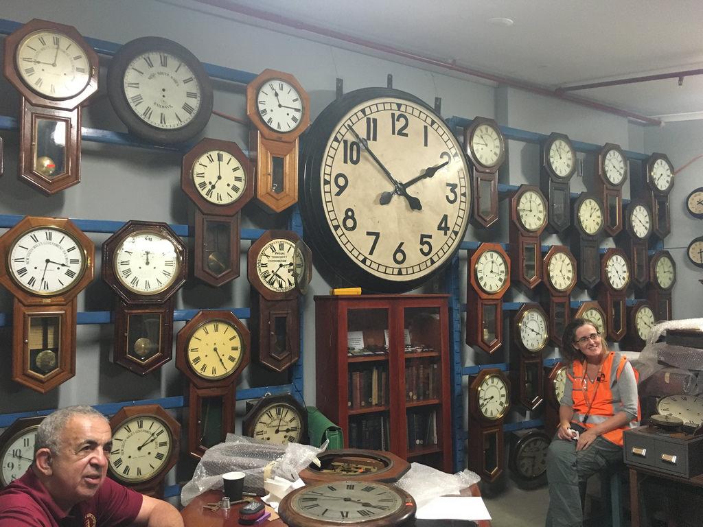 Auf dem Bild sind viele Uhren, eine Frau und ein Mann zu sehen