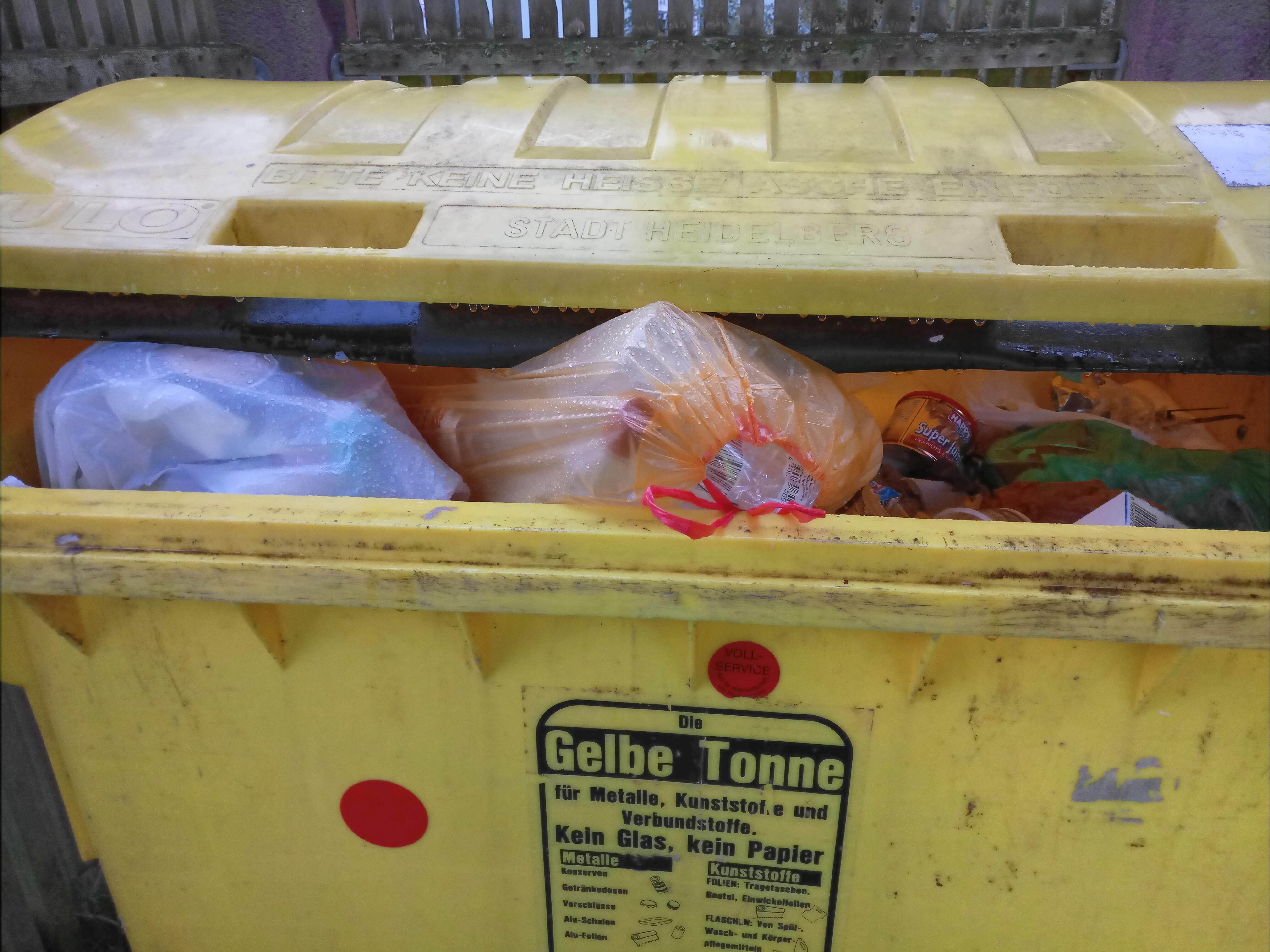 Eine Gelbe Tonne gefüllt mit Säcken.