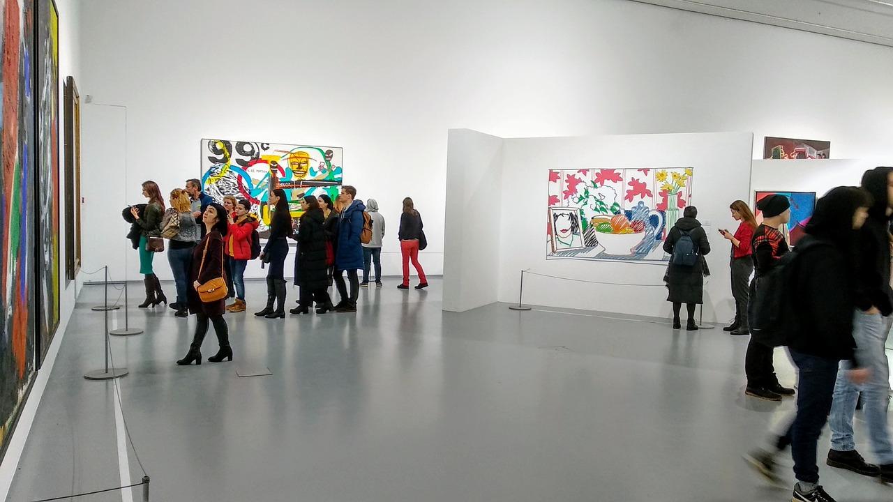 Auf dem Bild ist eine Kunst·ausstellung zu sehen. Besucher schauen sich Kunst·bilder von einem Künstler an.