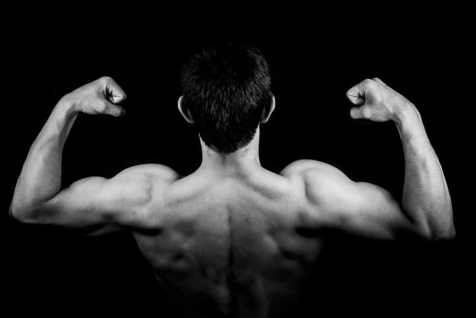 Auf dem Bild ist ein Mann. Er spannt seine Oberarme an. Damit man seine Muskeln sieht.